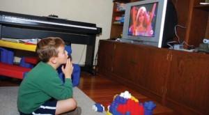 Niño varón ve en la televisión a la barbie, está absorto, hipnotizado; piano y juguetes son sólo partes del paisaje